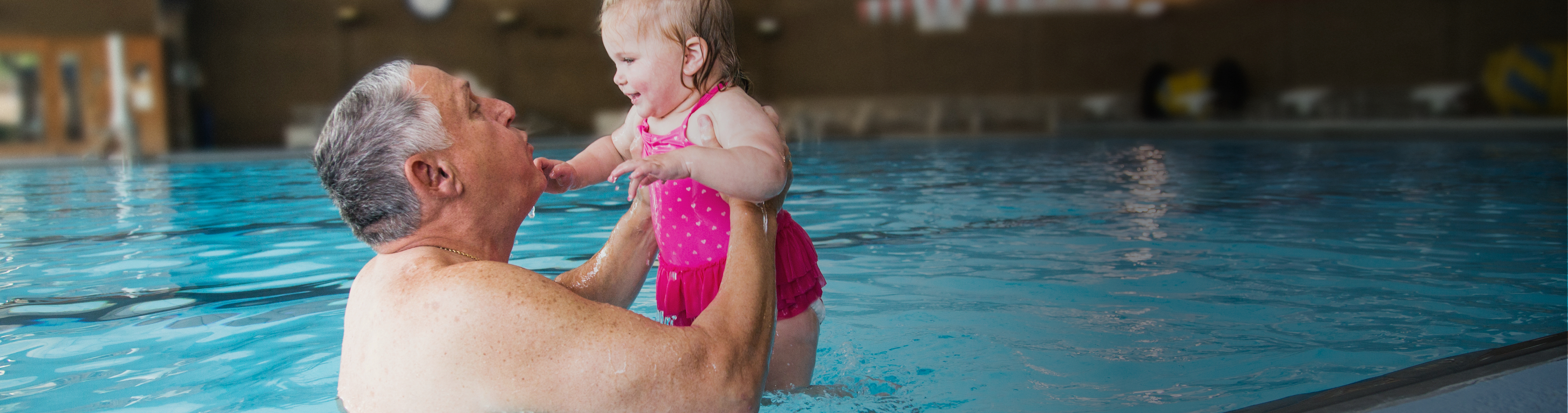 Grandfather playing in the pool with his granddaughter