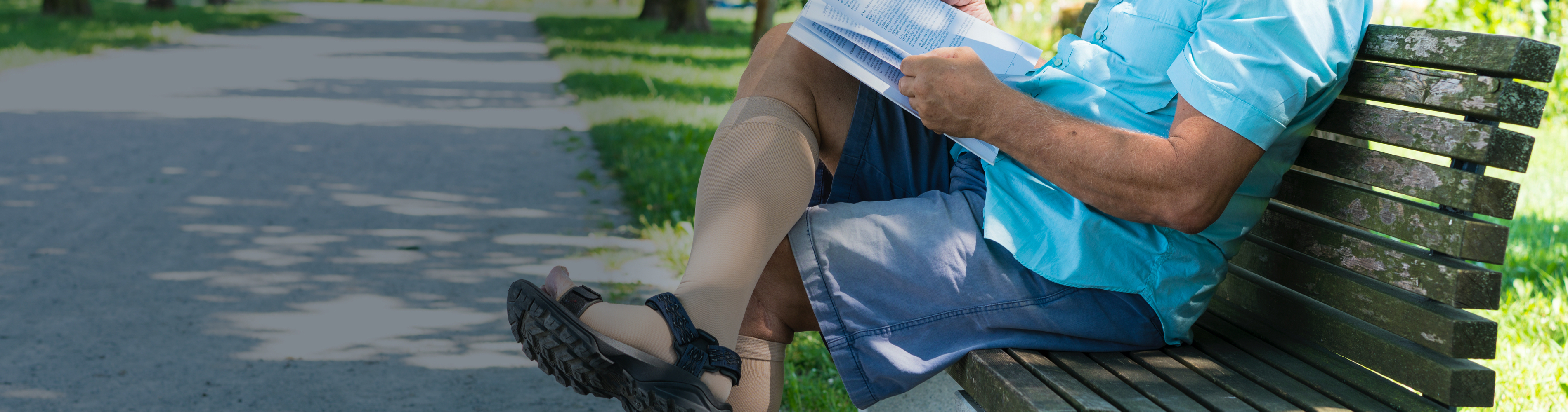 Man sitting on park bench wearing compression stockings